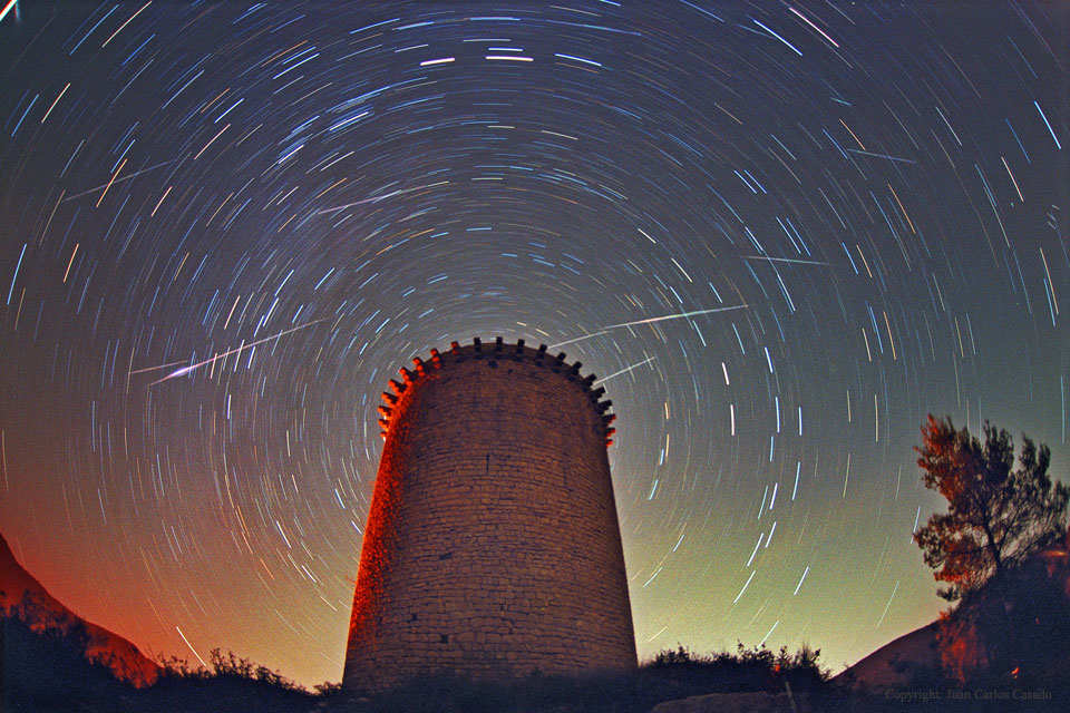 Leonid meteors streaking high above the Torre de la Guaita